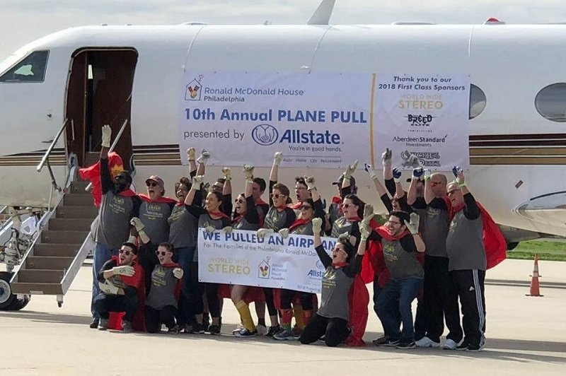The World Wide Stereo team celebrates after pulling a plane and raising $12,000 for the Ronald McDonald House
